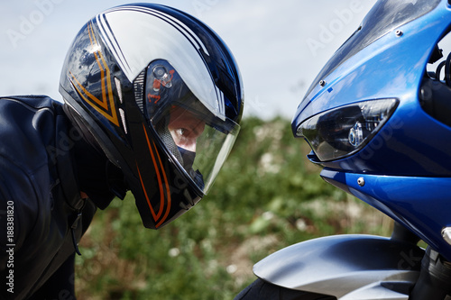 Fototapeta Close up sideways view of blue motorcycle and self determined young male rider wearing black leather jacket and stylish protective helmet getting ready for race