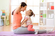 Mother and child daughter engaged in fitness, yoga, exercise at home