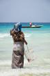 Woman waiting for fishing boat to come into shore in Stone Town, Zanzibar Island, Tanzania.