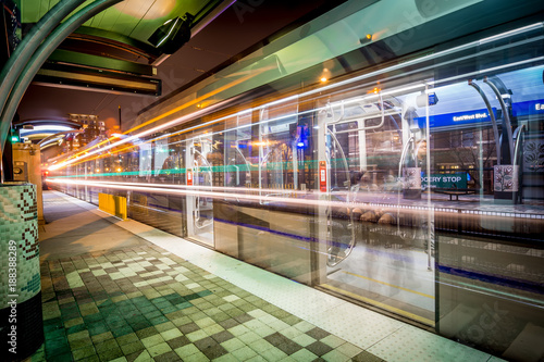 Fotografering  Charlotte City Skyline night scene with light rail system lynx train