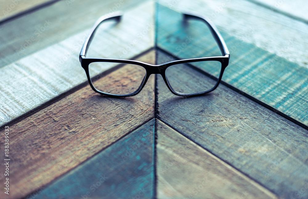 Fototapeta Modern black designer eyeglasses on weathered wood surface with angular pattern.