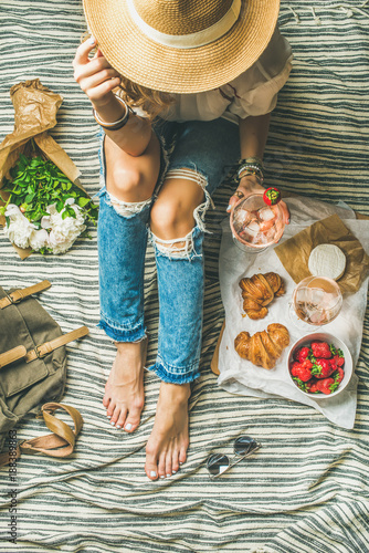 Keuken foto achterwand French style romantic picnic setting. Woman in shabby jeans with glass of ice rose wine, strawberries, croissants, brie cheese, hat, sunglasses, peony flowers, top view. Outdoor gathering concept