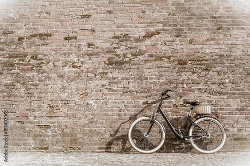 Fotobehang Fiets Black retro vintage bicycle with old brick wall.
