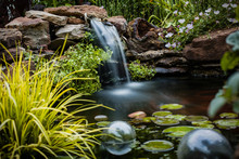 A Lush Koi Pond Surrounded By Stones And Plants With A Misty Waterfall