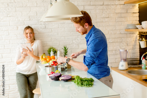 Poster Cuisine Young couple have fun in modern kitchen indoor while preparing vegetables food for lunch