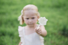 Girl Showing White Flowers While Standing On Grassy Field At Park