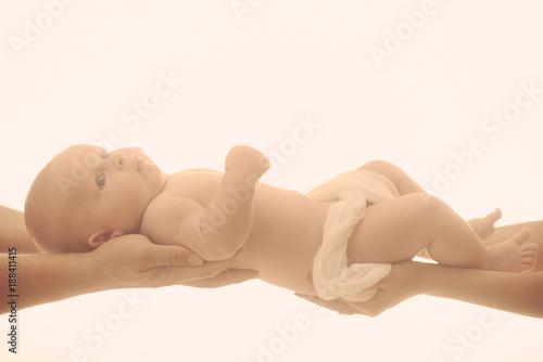 Photo  Newborn baby lies awake in diaper on parent hands.