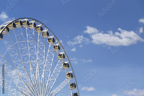 Giant Ferris wheel with numbered cabins in the park - Bright blue sky with sharp clouds behind it Wallpaper Mural