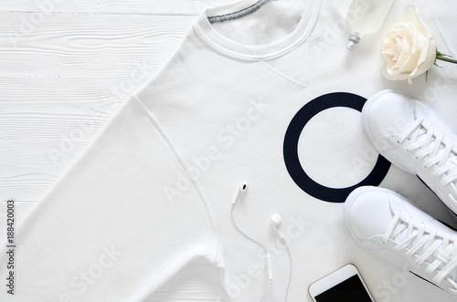 Fototapeta Womens fashion white clothing, shoes, accessories (white leather sneakers, blue jeans, sweatshirt, headphones, perfume, flowers. Fashion concept. View from above, Flat lay. Spring summer collection obraz