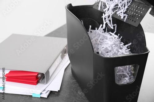 Fotografie, Obraz  Document shredder with paper shreds on table, closeup