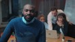 Young attractive African man in blue sweater looking at camera and smiling on background of working colleagues. Office. Evening time.