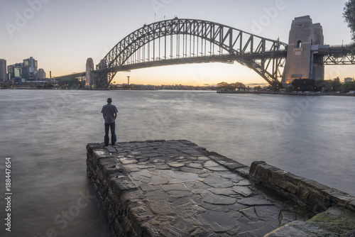 Man standing alone in Sydney Harbor looking over Sydney Harbor Bridge at dusk, Sydney, New South Wales, Australia