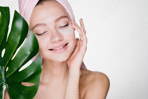 Fotografía cute young girl with a pink towel on her head enjoying a spa, under eyes patches