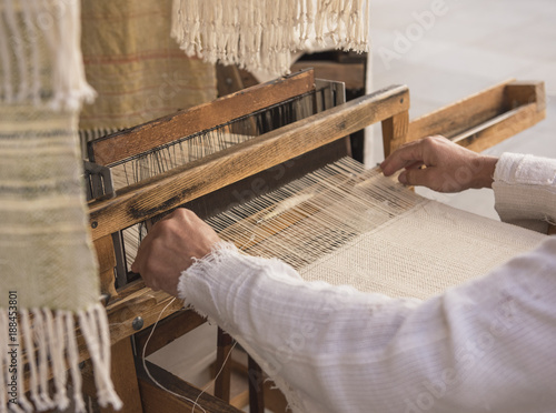 Slika na platnu Hands of a man weaving on a loom