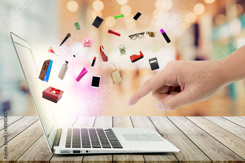 Fotografía  Shopping cart and laptop computer with products on wood bokeh background, shop online concept