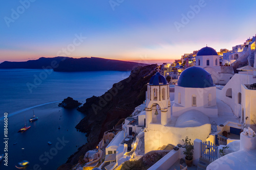 Staande foto Europese Plekken Cityscape of Oia, traditional greek village with blue domes of churches, Santorini island, Greece at dusk.
