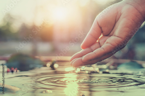 Foto auf Gartenposter Wasser hand and water with sunset