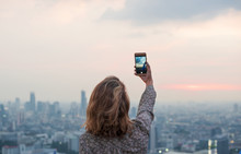 Woman Taking A Photo Of The Sunset