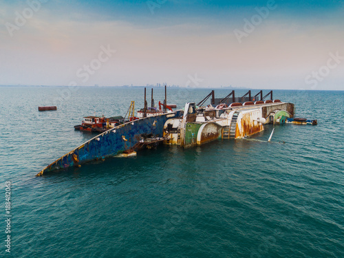 Tuinposter Schipbreuk a sink passenger ship lie down in middle of the sea under cutting scrap iron, useless and wreckage junk ship for rid of detroy away from pollution