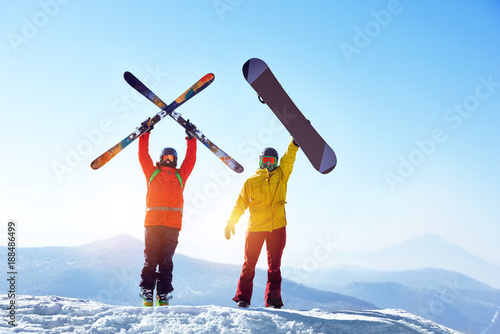 Fotobehang Wintersporten Active skier and snowboarder against mountains