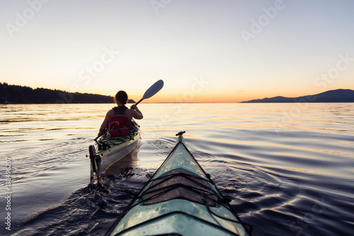 Adventure Woman Kayaking on a Sea Kayak during a Vibrant Sunset. Taken near Jericho Beach, Vancouver, BC, Canada.