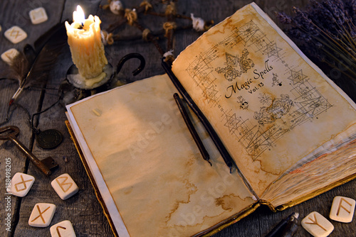 Open old book with magic spells, runes, candle and key on
