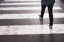 Low Section Of A Pedestrian Crossing The Road From The Marked Crosswalk