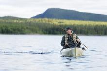 Man Fishing In Lake From Kayak