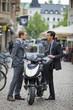 Men in suits talking near scooter
