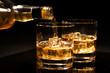 Leinwanddruck Bild - pouring whiskey into a glass with ice cubes on black background