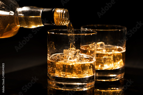 Poster Alcohol pouring whiskey into a glass with ice cubes on black background
