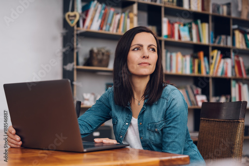 Thoughtful woman sitting working in a library Wallpaper Mural