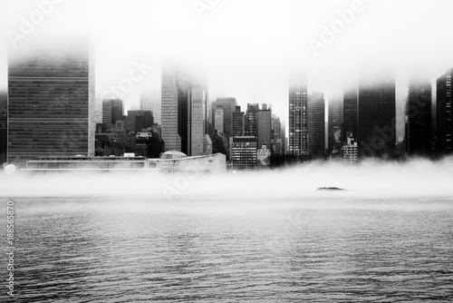 Wall Murals New York A dense fog covered New York City during the winter's day on January of 2018. View of Manhattan and United Nations building.