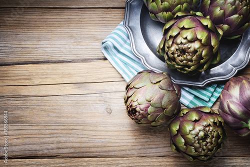 Artichokes on a wood background. Top view with space for text Canvas Print