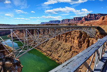 Navajo Bridge Across The Colorado River At Glen Canyon With Red Rock Mountains In The Background
