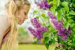 lovely girl smelling lilac flower