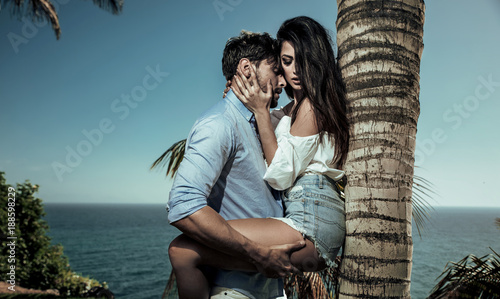 Portrait of attractive lovers leaning on a palm tree Fototapet