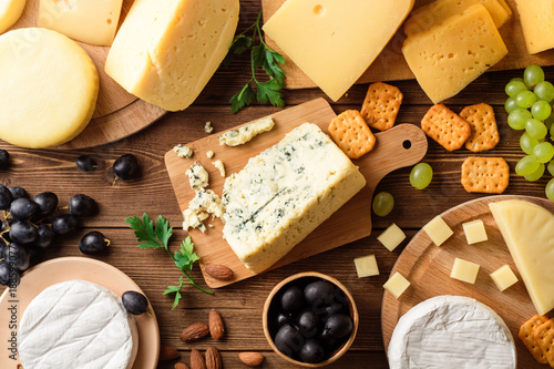 Fotoposter Zuivelproducten Various types of cheese on dark rustic wooden background.