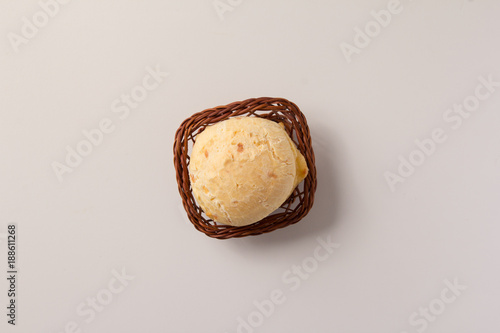 Fototapeta Pao de Queijo is a cheese bread ball from Brazil. Also known as Chipa, Pandebono and Pan de Yuca. One snack in basket over white background, minimalism. obraz na płótnie