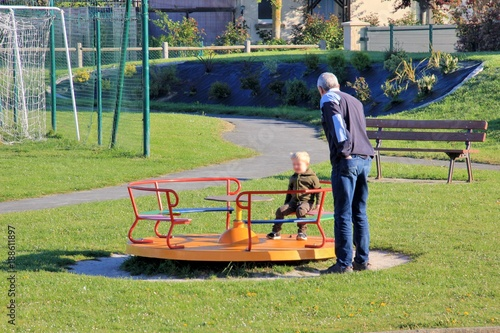 Fotografie, Obraz  Un grand-père joue avec son petit-fils dans un square