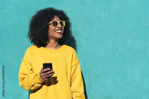 fototapeta na drzwi i meble Beautiful afro american woman using mobile in the street.