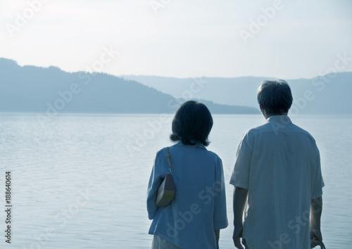 湖を旅行で訪れたシニア夫婦の後姿