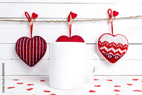 White coffee mug with decorative red hearts. Space for text or design.