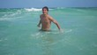 Young handsome happy man swimming in crystal blue sea and splashing wave in slow motion. 1920x1080