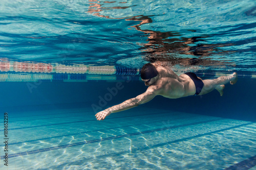 Papiers peints underwater picture of young swimmer in cap and goggles training in swimming pool
