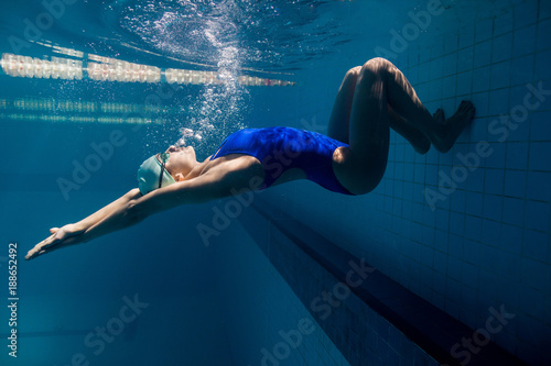 Obraz underwater picture of young female swimmer exercising in swimming pool - fototapety do salonu