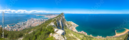 Leinwand Poster Panorama of top of Gibraltar Rock, in Upper Rock Natural Reserve: on the left Gibraltar town and bay, La Linea town in Spain at the far end, Mediterranean Sea on the right