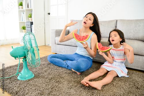 Fotografia young mother with cute little daughter feeling hot