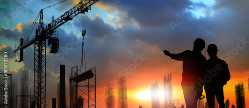 two engineer on working site , engineer and tower cranes at construction site and city background