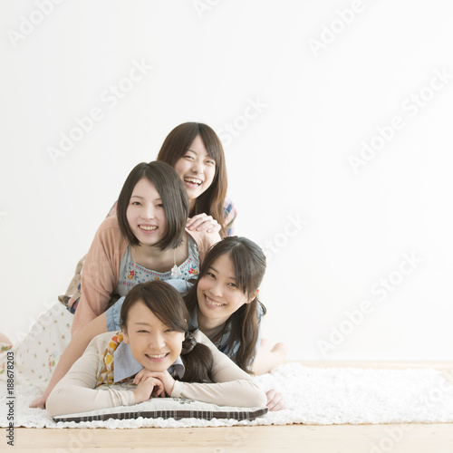 床に寝転び微笑む4人の女性